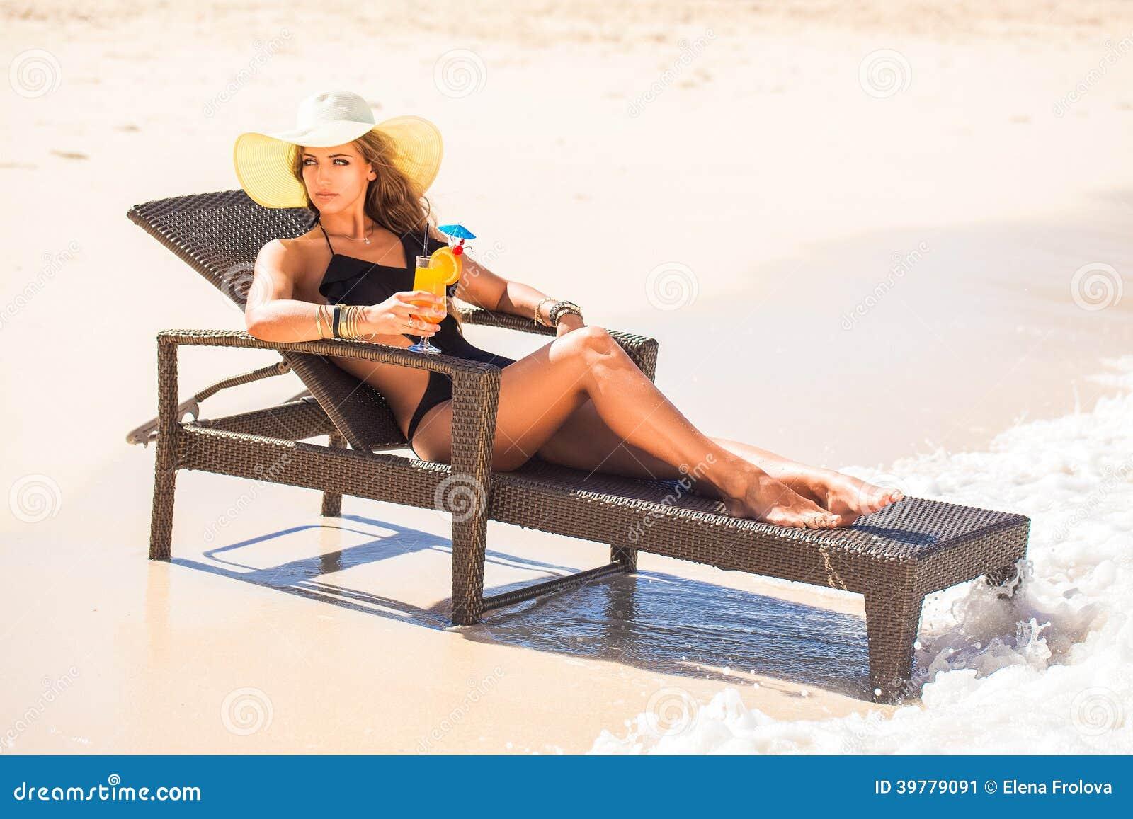 Jovem mulher no chapéu de palha que coloca na praia e no enjoyi tropicais