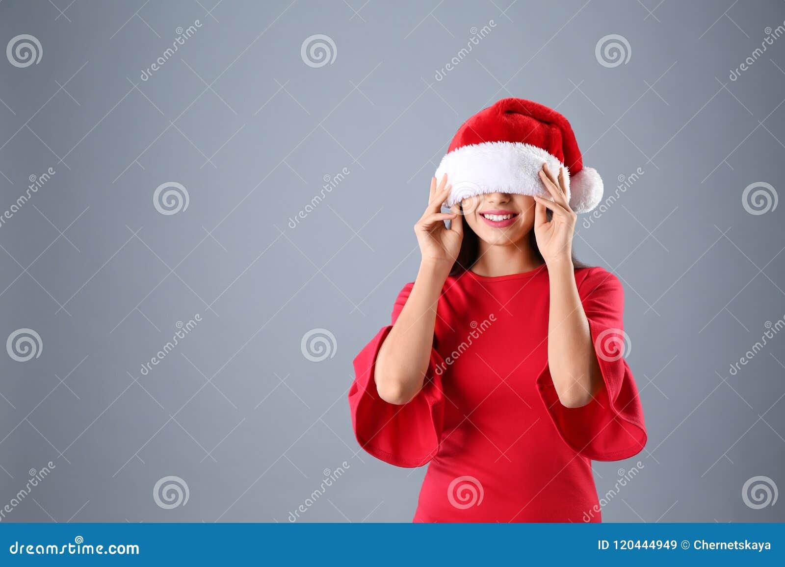 Jovem mulher no chapéu de Santa no fundo cinzento Celebração do Natal
