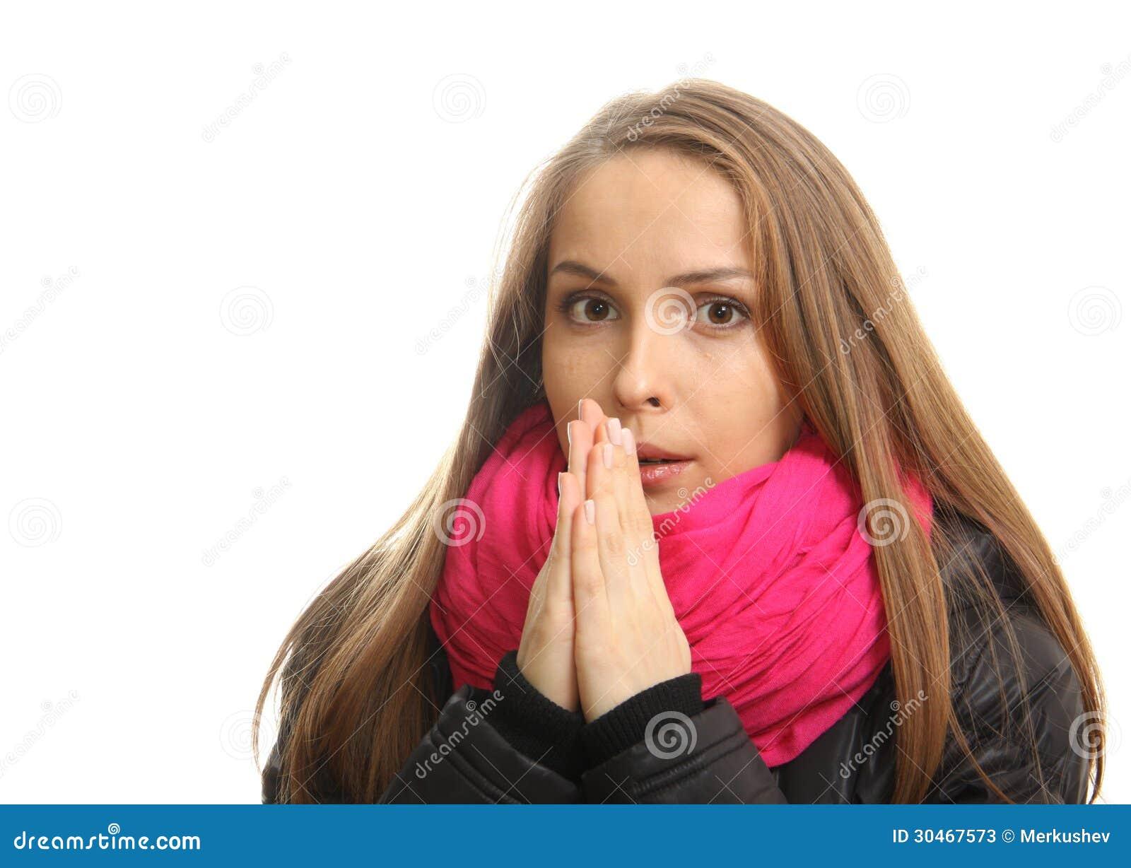 A jovem mulher no inverno tenta aquecer suas mãos