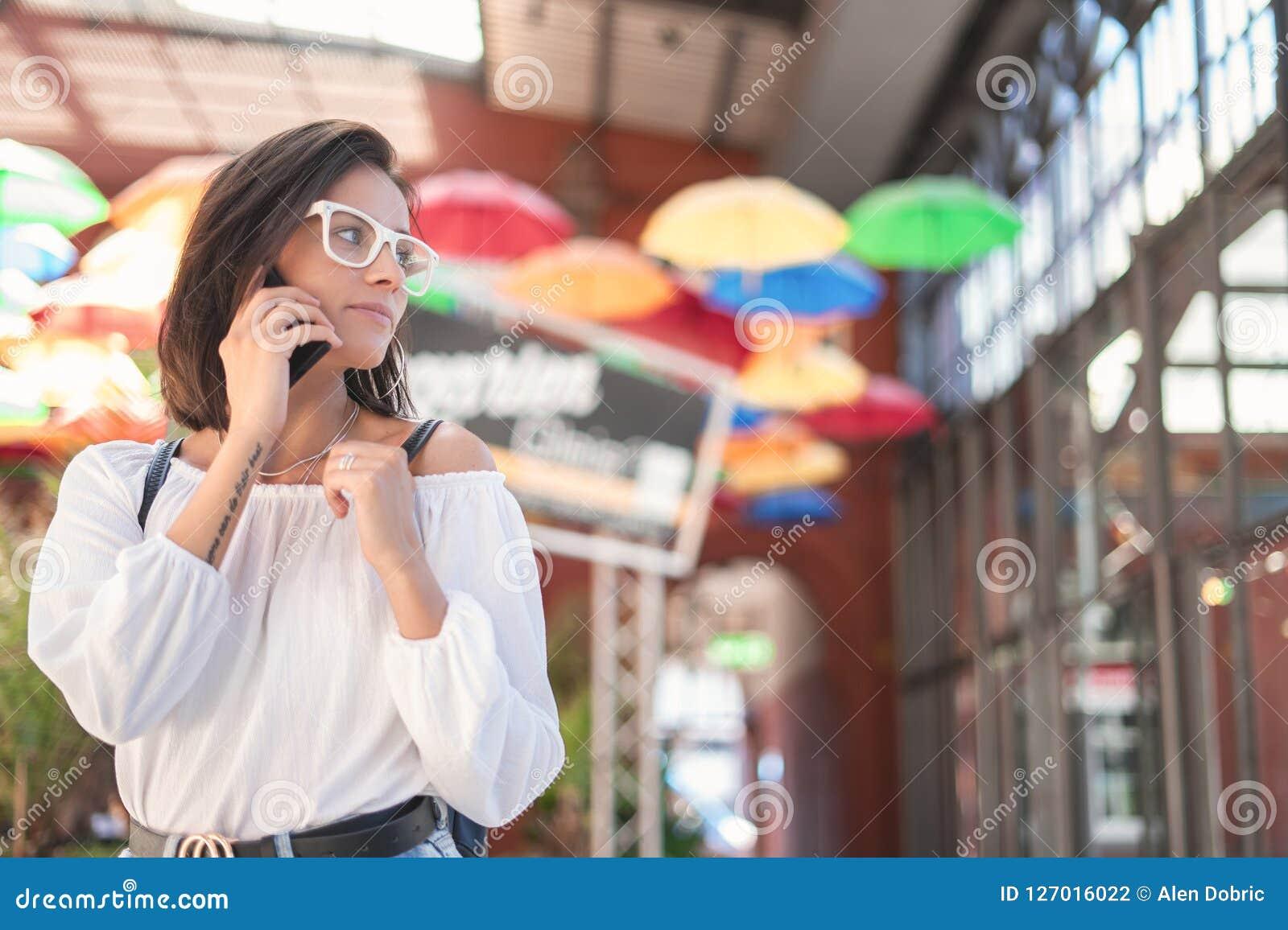 Jovem mulher no smartphone que olha ao lado