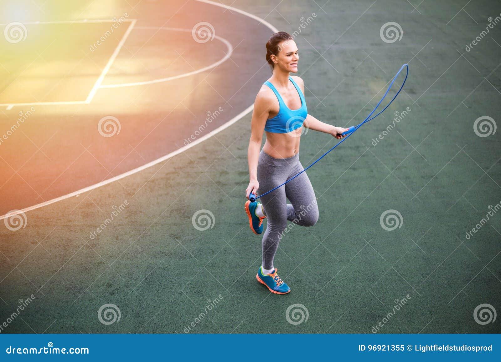 Jovem mulher no sportswear que exercita com corda de salto no estádio