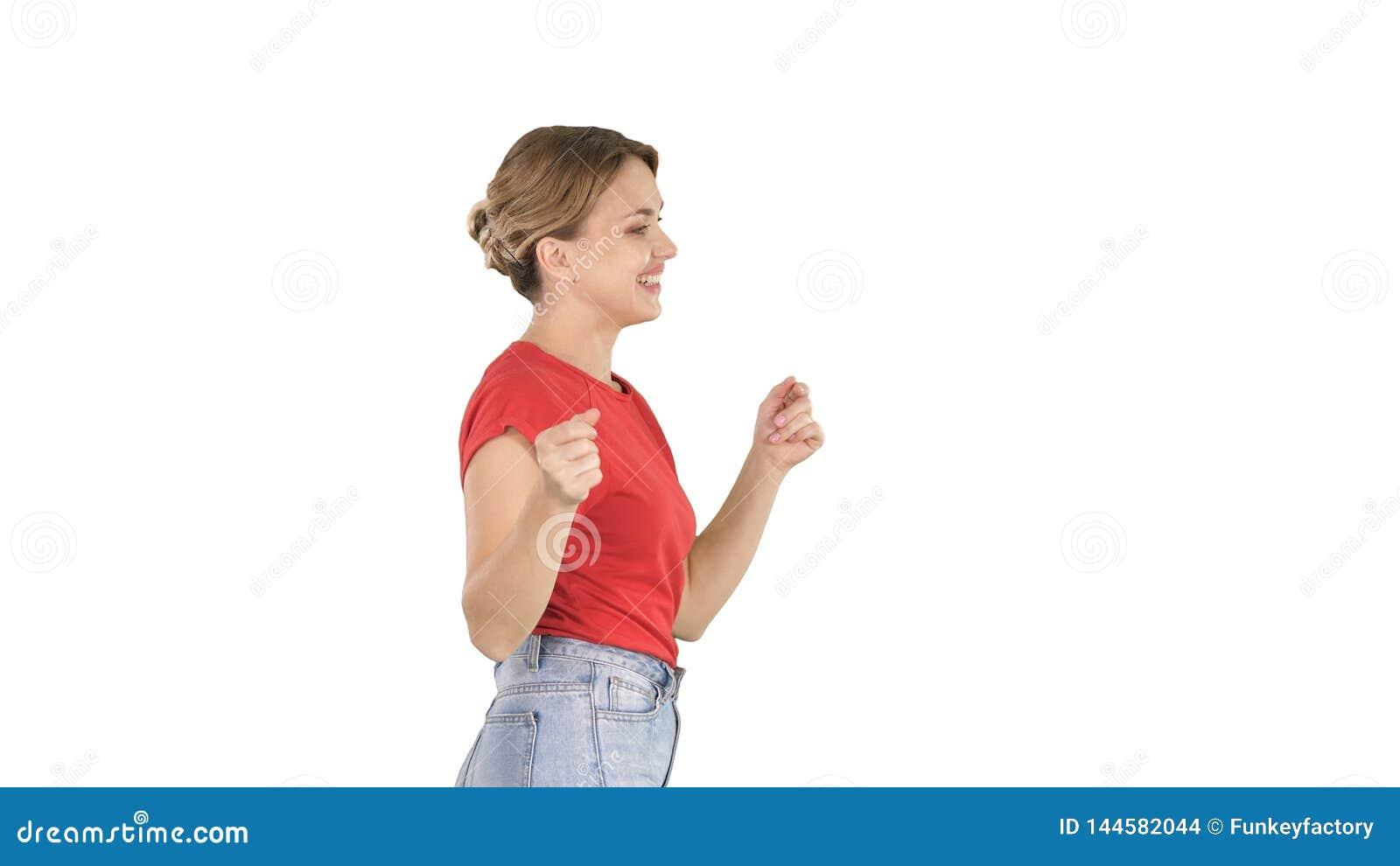 Jovem mulher no t-shirt vermelho, calças de brim que dançam e que andam no fundo branco