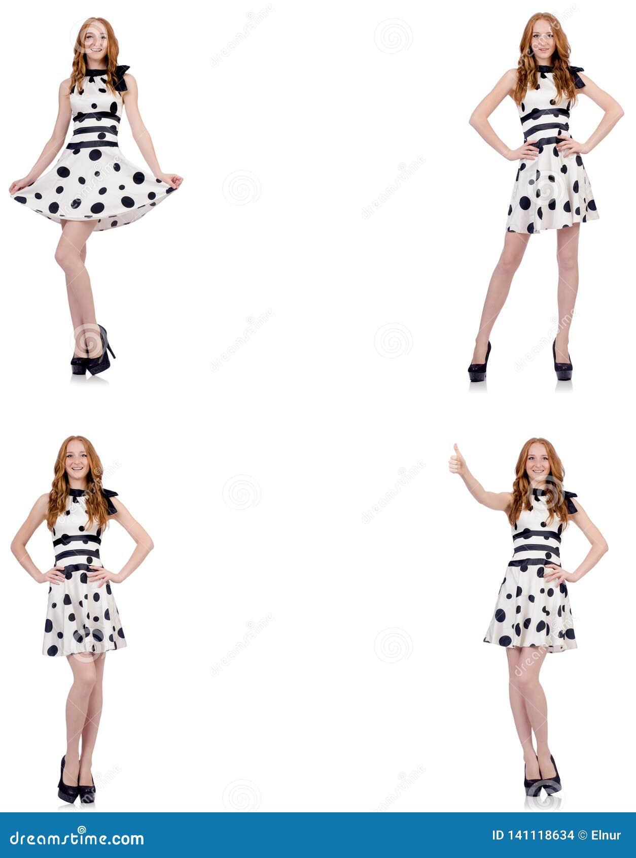 A jovem mulher no vestido do às bolinhas isolado no branco