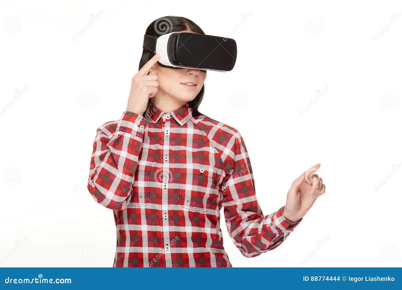 Jovem mulher nos auriculares de VR que passa o tempo no Cyberspace
