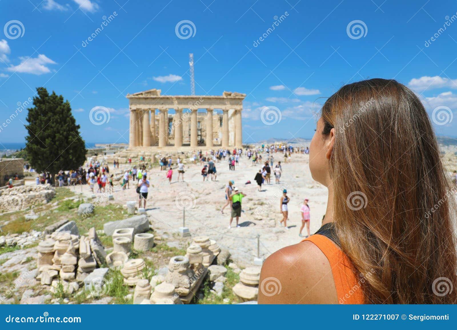 A jovem mulher olha o Partenon na acrópole de Atenas, Grécia O Partenon famoso do grego clássico é o turista principal
