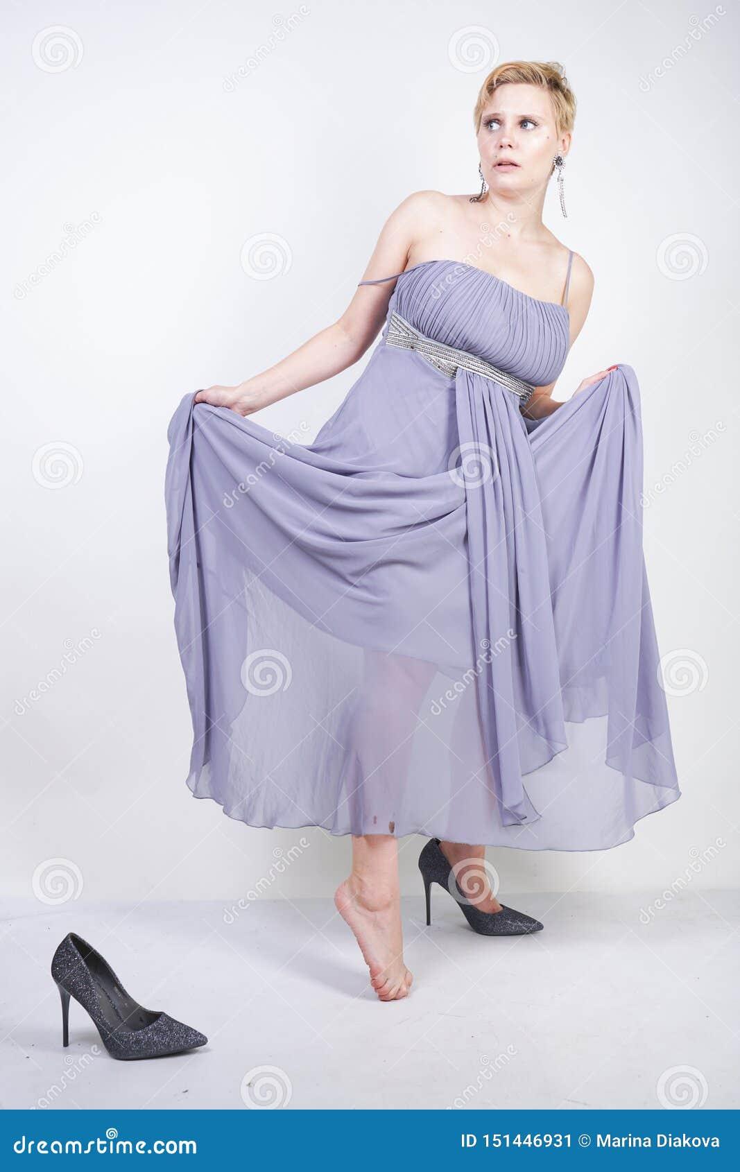 A jovem mulher positiva de encantamento do tamanho no vestido cinzento do vestido perdeu o deslizador no fundo branco no estúdio