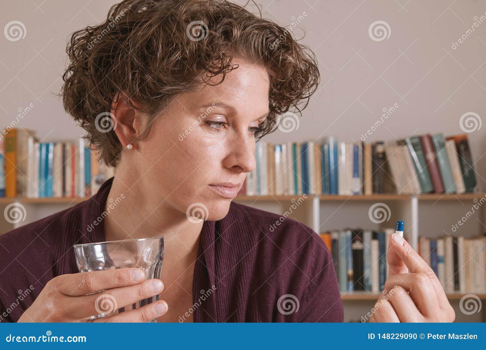 A jovem mulher preocupou-se sobre a tomada do comprimido