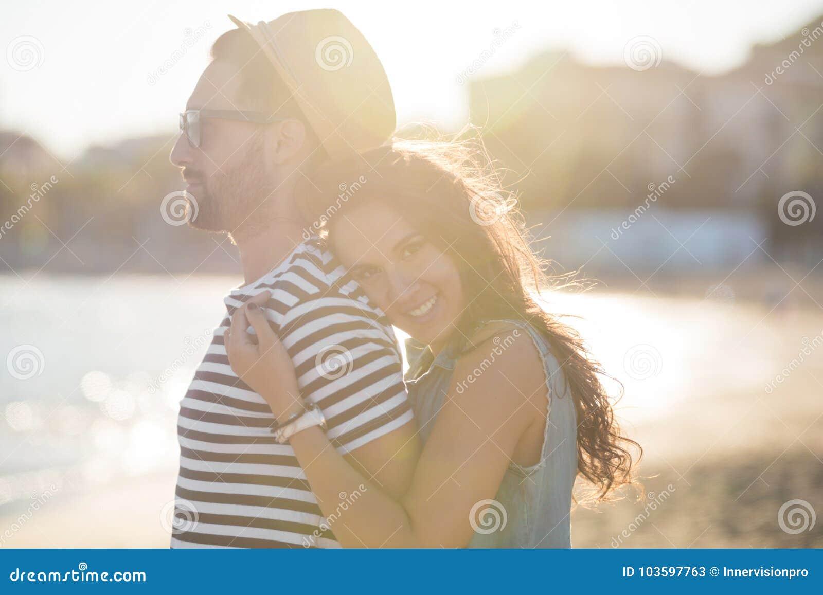Jovem mulher que abraça seu noivo no sorriso do beira-mar
