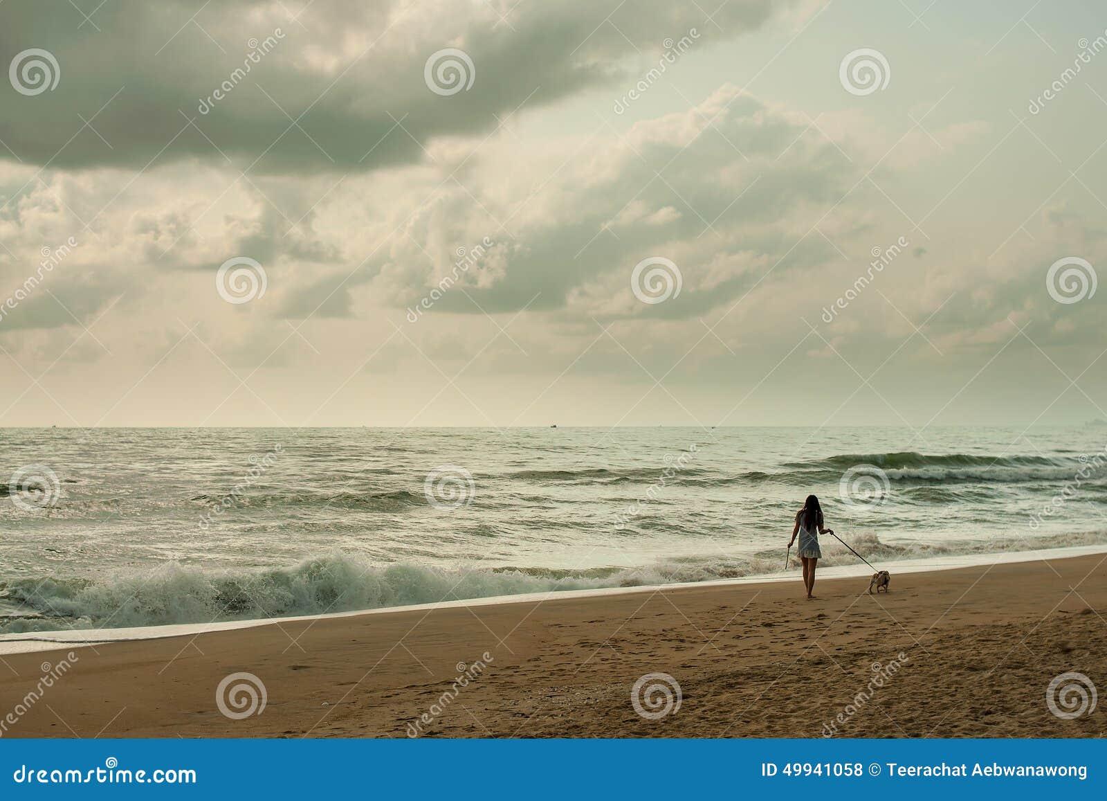 Jovem mulher que anda com seu cão na praia com céu bonito (estilo retro)