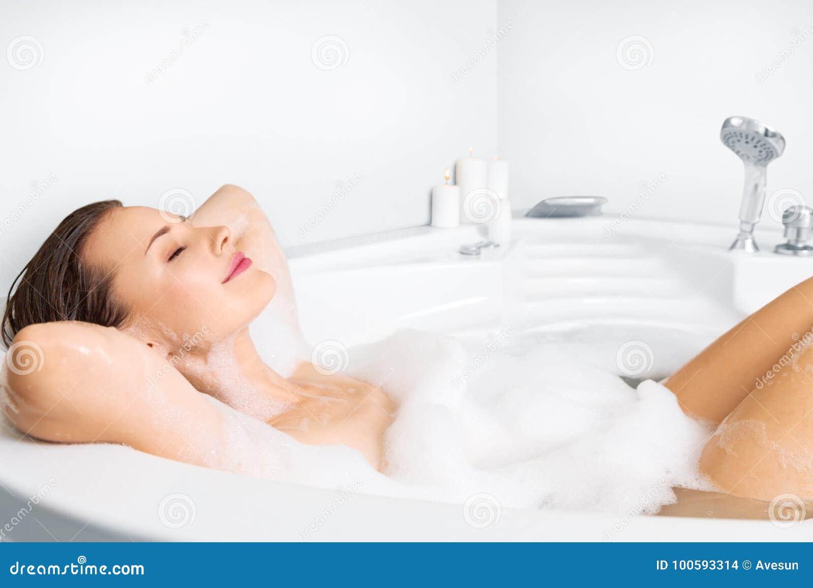 Jovem mulher que aprecia o banho na banheira