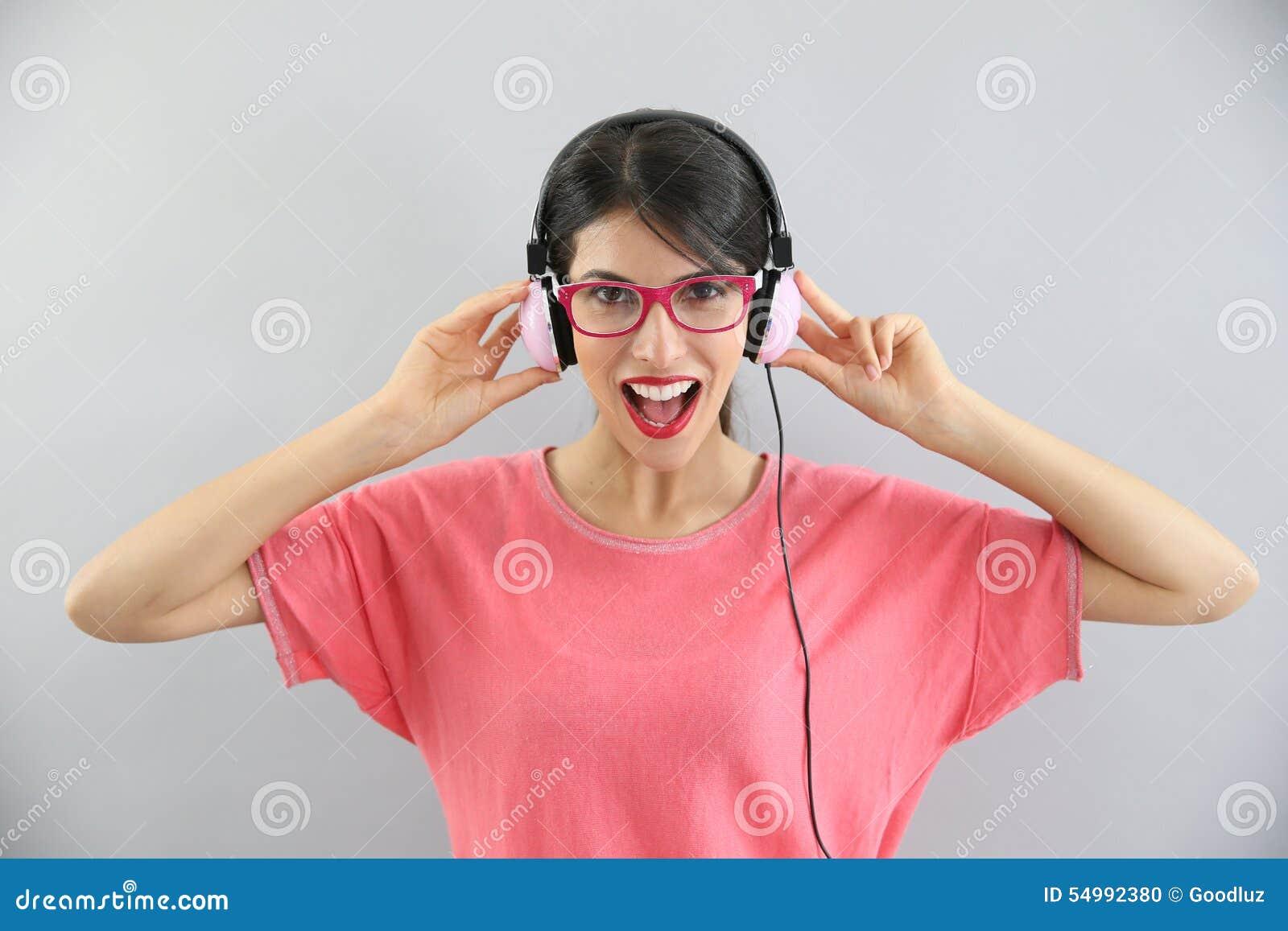 Jovem mulher que canta com fones de ouvido sobre
