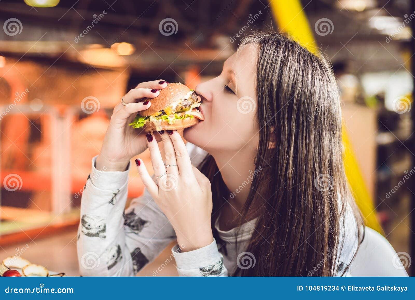 Jovem mulher que come a mulher do Hamburger que come a comida lixo, alimento gordo
