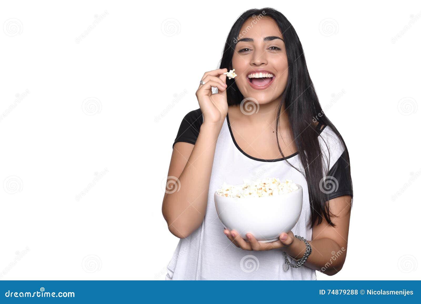 Jovem mulher que come a pipoca