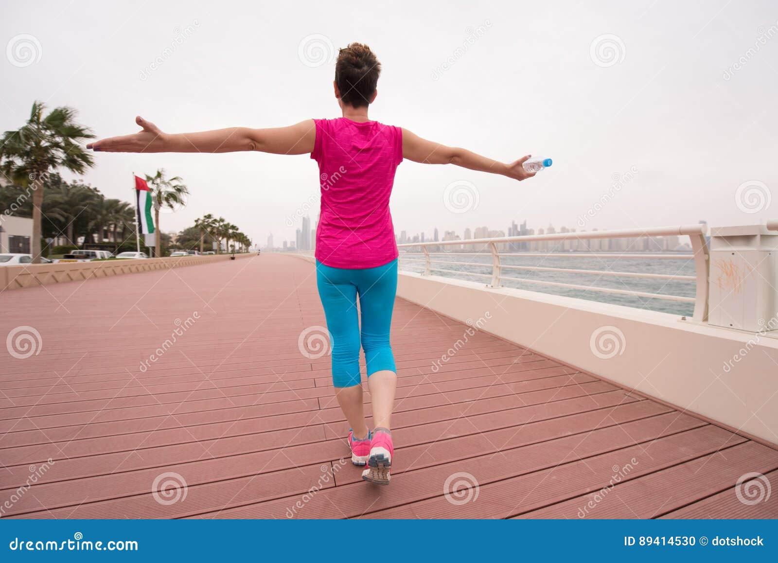 Jovem mulher que comemora uma corrida bem sucedida do treinamento
