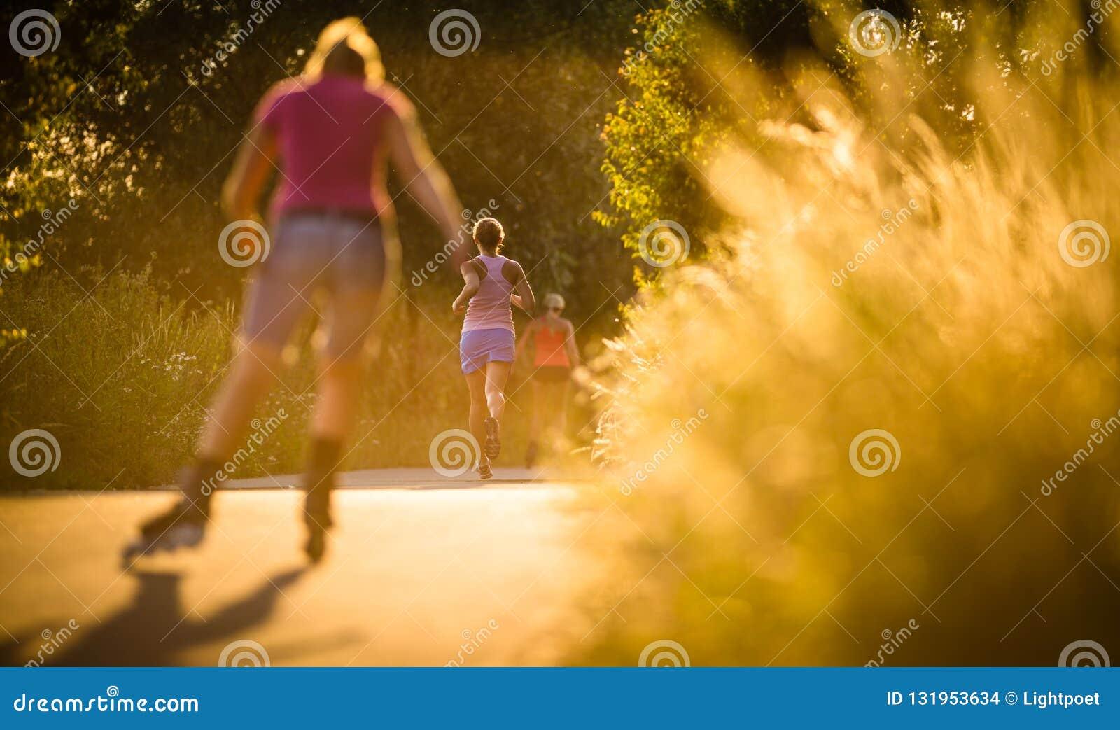 Jovem mulher que corre fora em evenis ensolarados bonitos de um verão