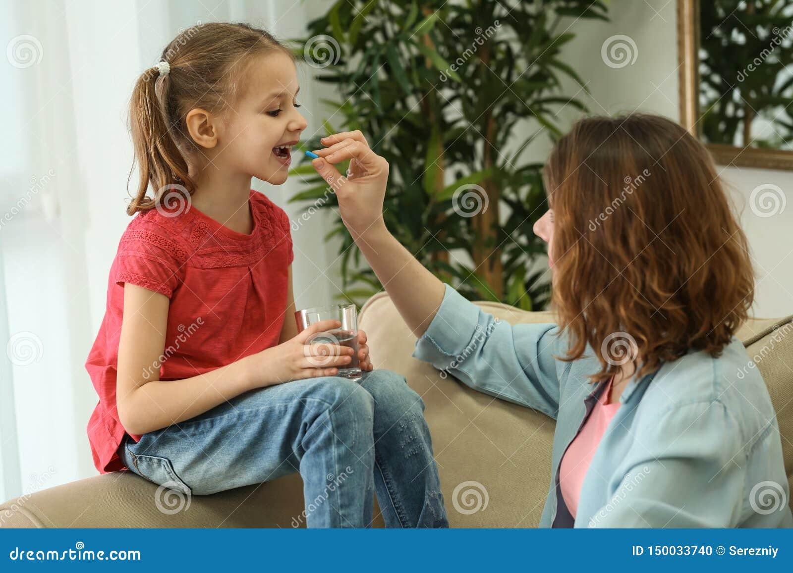 Jovem mulher que dá o comprimido a sua filha em casa