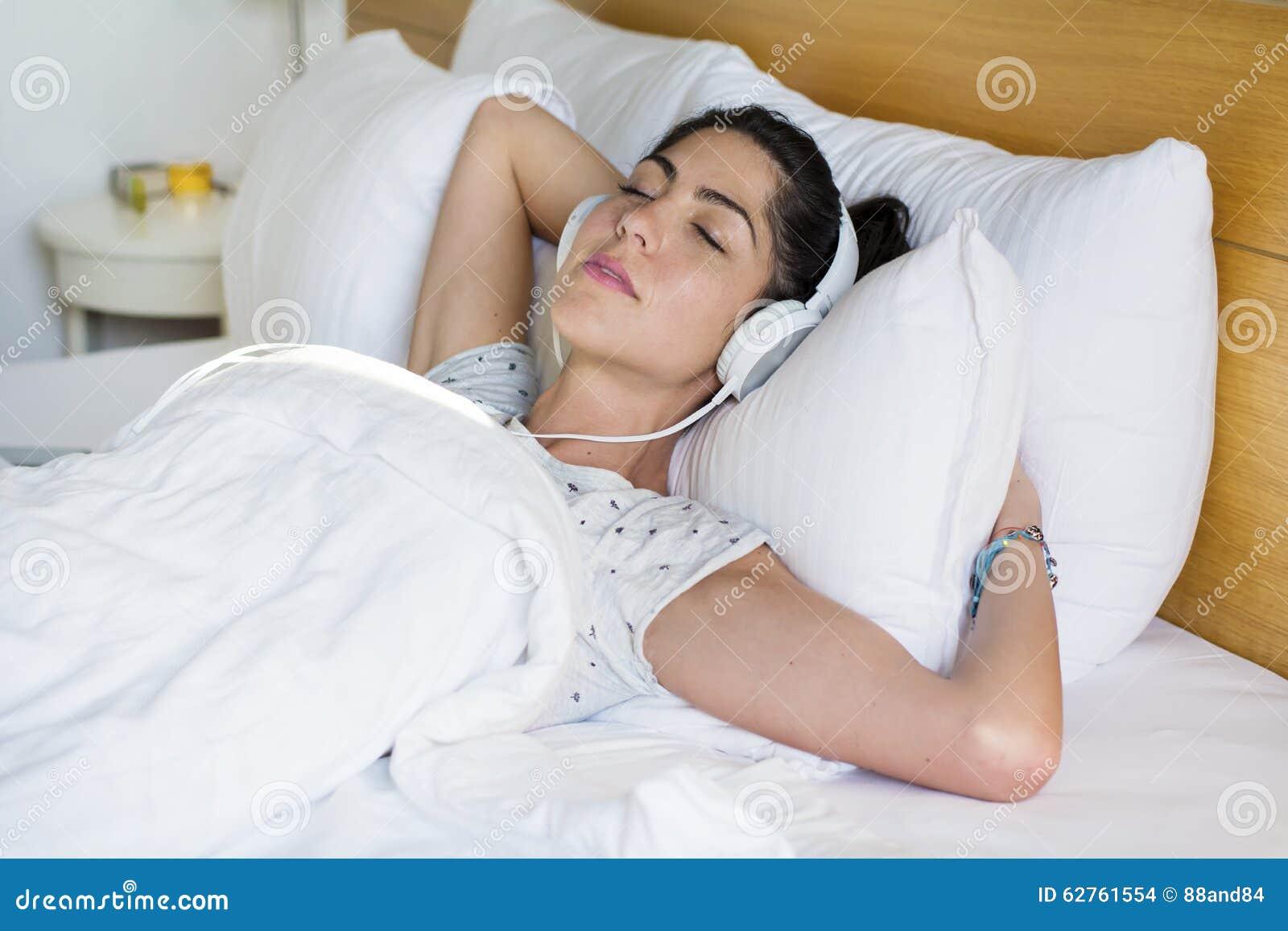 Jovem mulher que dorme na música de escuta da cama
