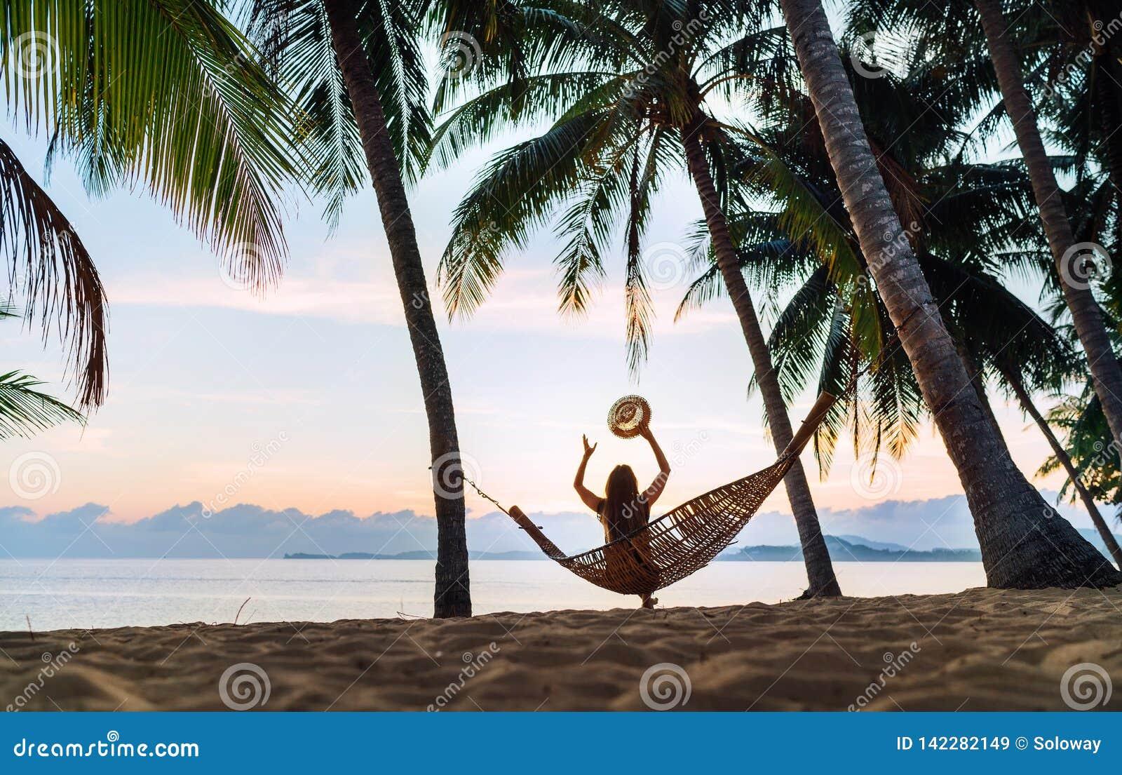Jovem mulher que encontra o nascer do sol que senta-se na rede na praia da areia sob as palmeiras