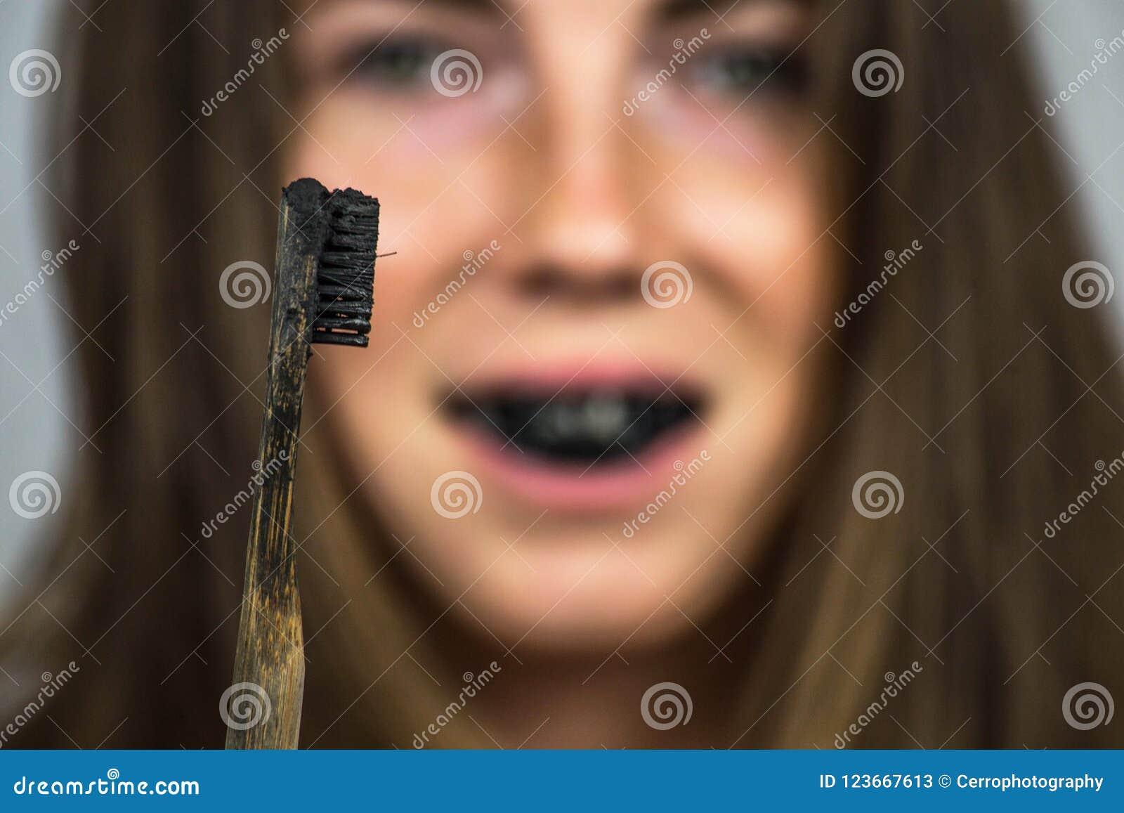 Jovem Mulher Que Escova Seus Dentes Com Uma Pasta De Dente Preta Com