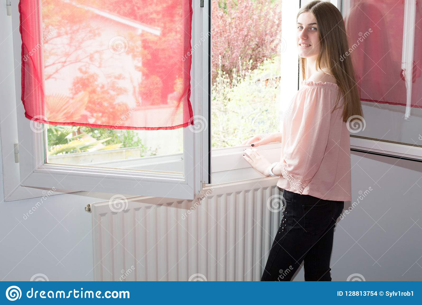 Jovem mulher que está a janela home próxima do quarto