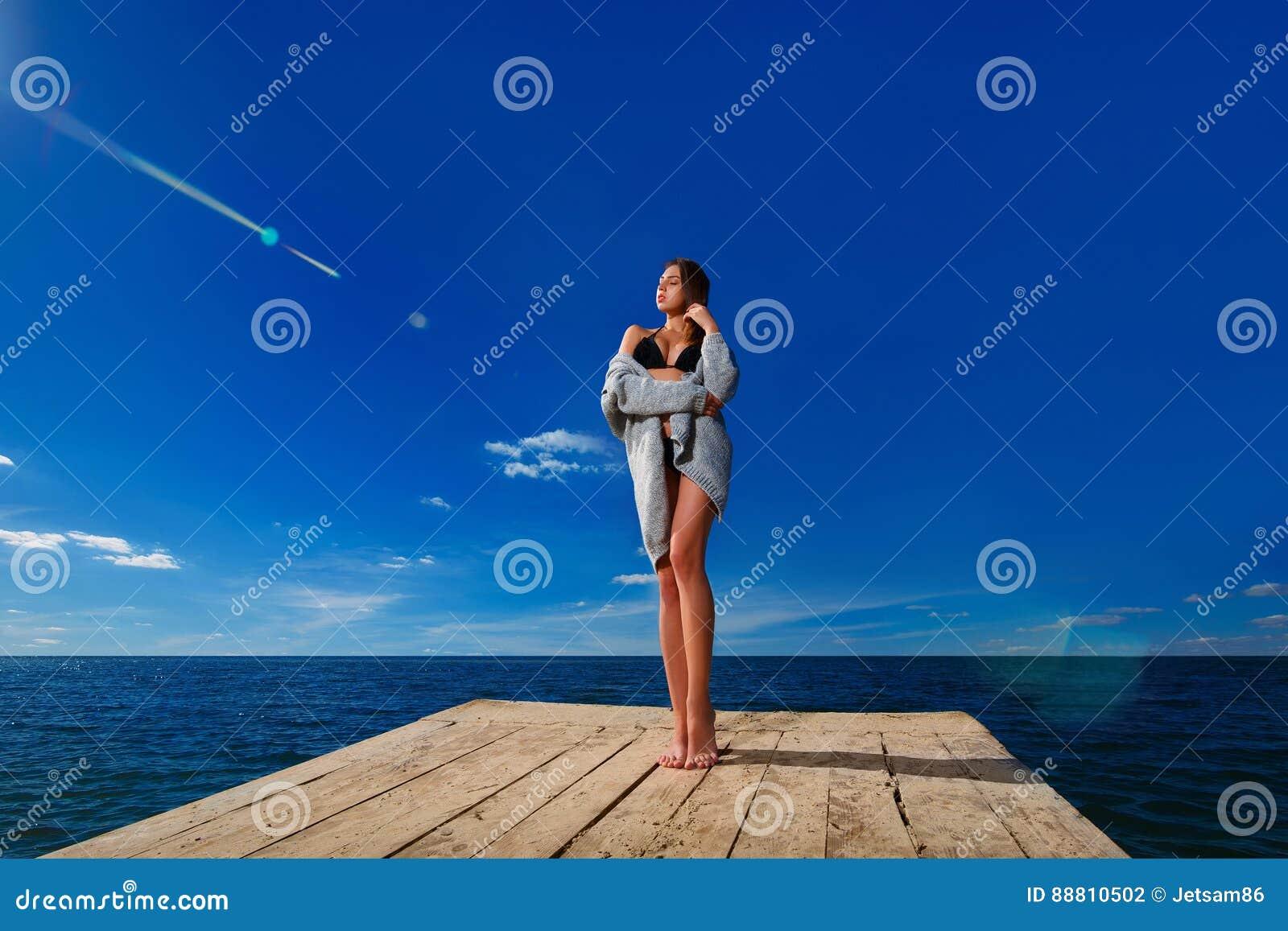 Jovem mulher que está no cais de madeira