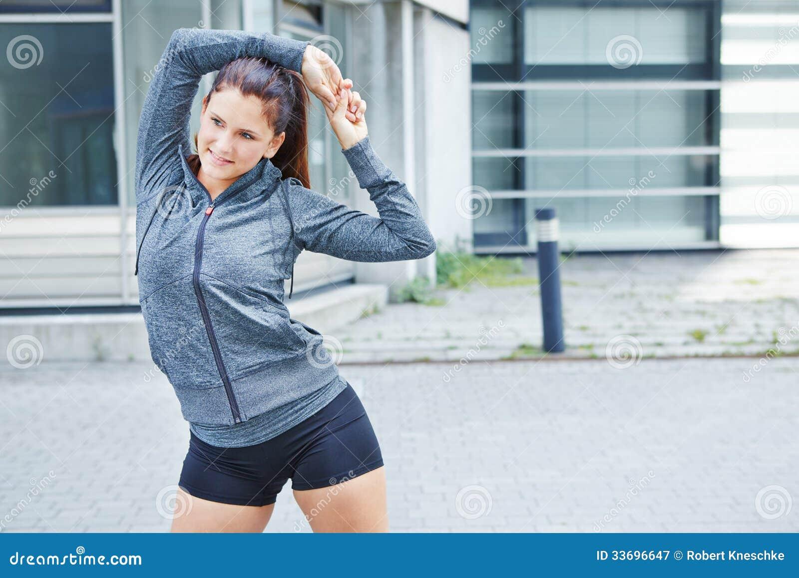 Jovem mulher que estica antes de treinar