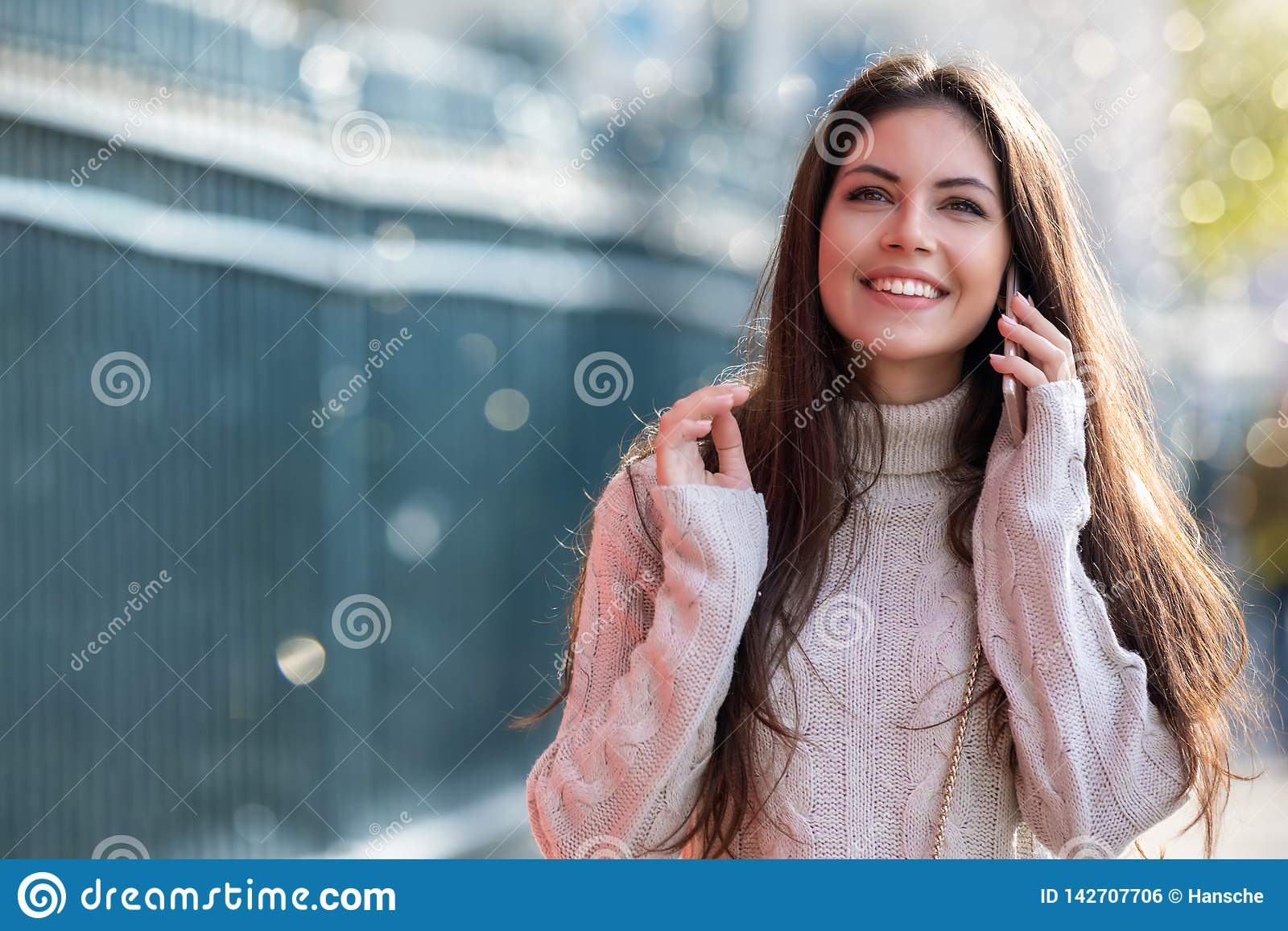 Jovem mulher que fala em seu telefone celular na cidade