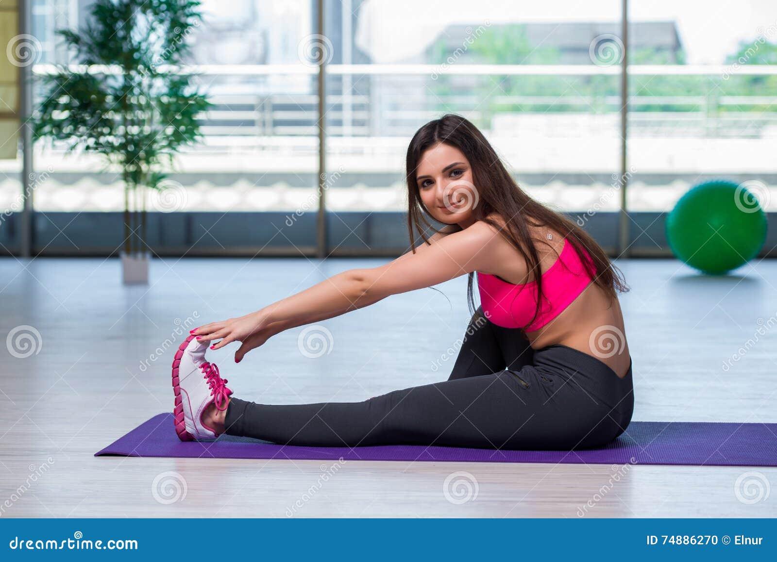 A jovem mulher que faz exercícios no conceito da saúde do gym