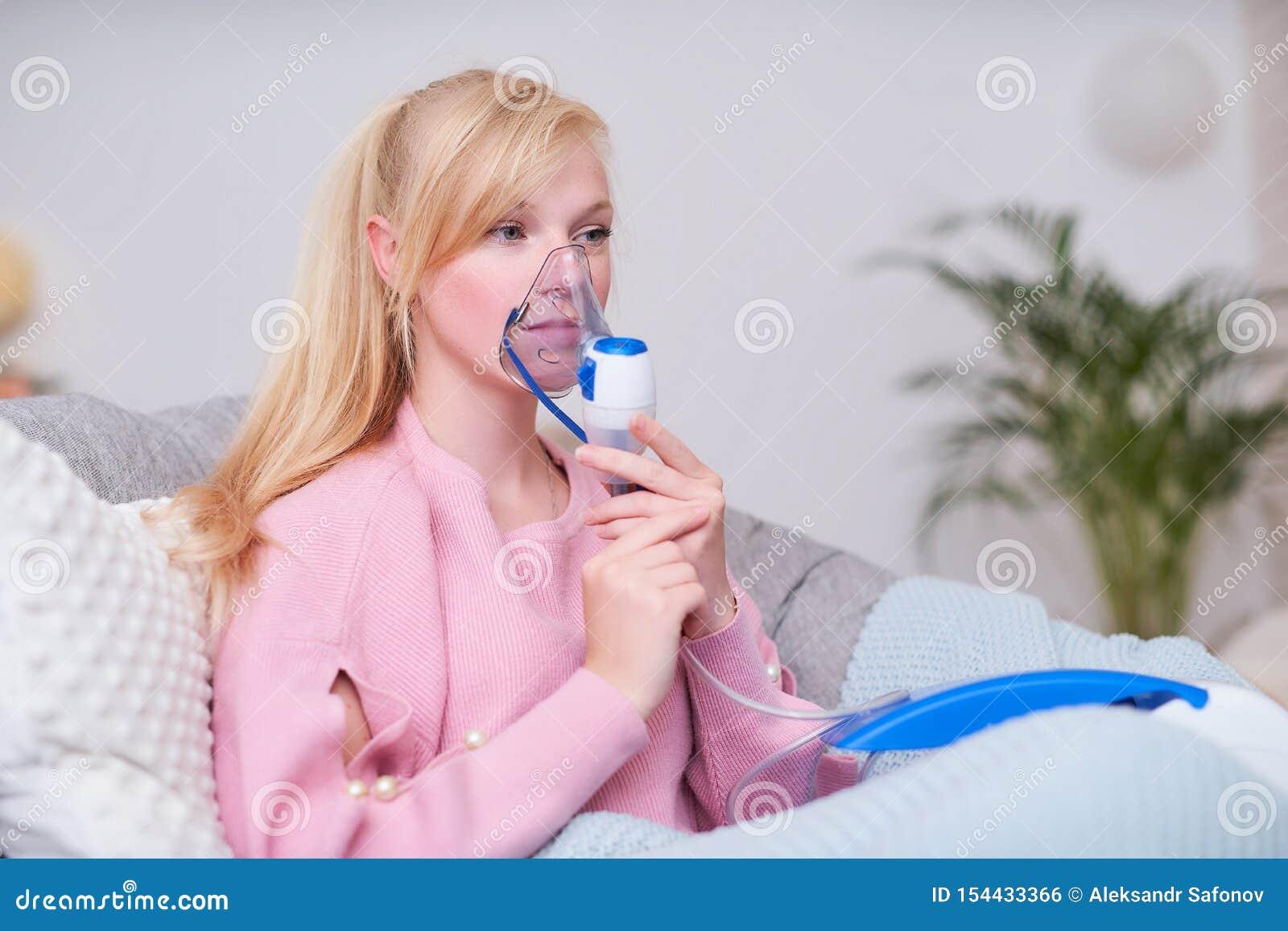 Jovem mulher que faz a inala??o com um nebulizer em casa