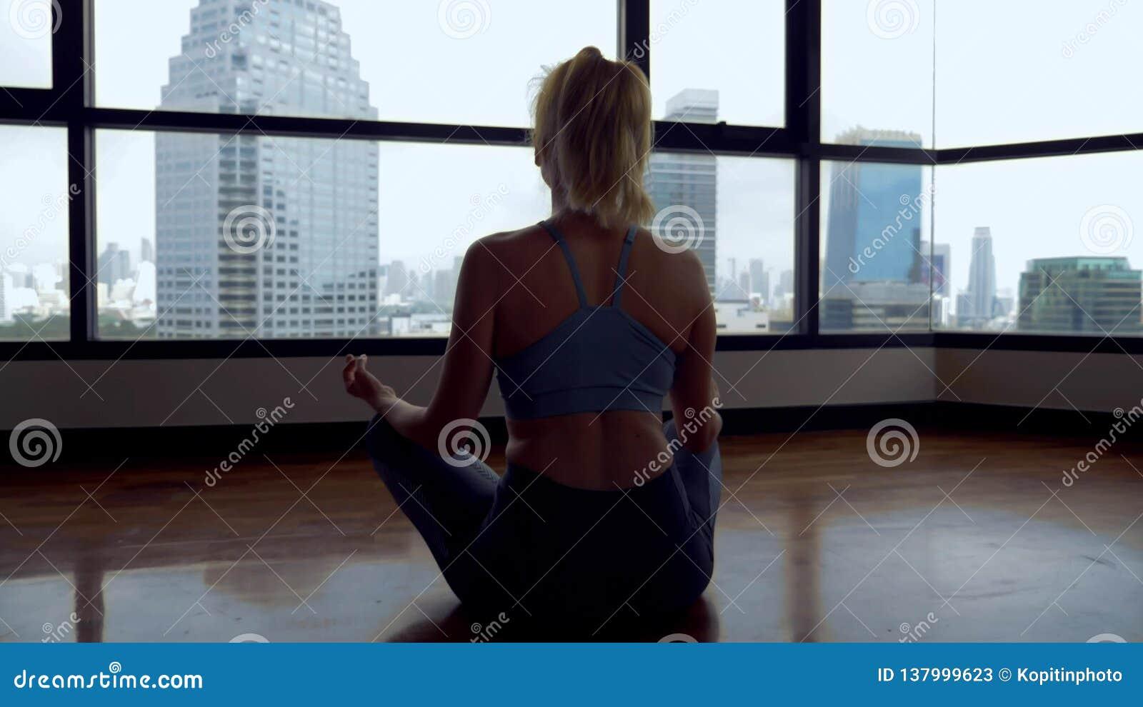 Jovem mulher que faz a ioga em uma sala perto de uma grande janela que negligencia os arranha-céus