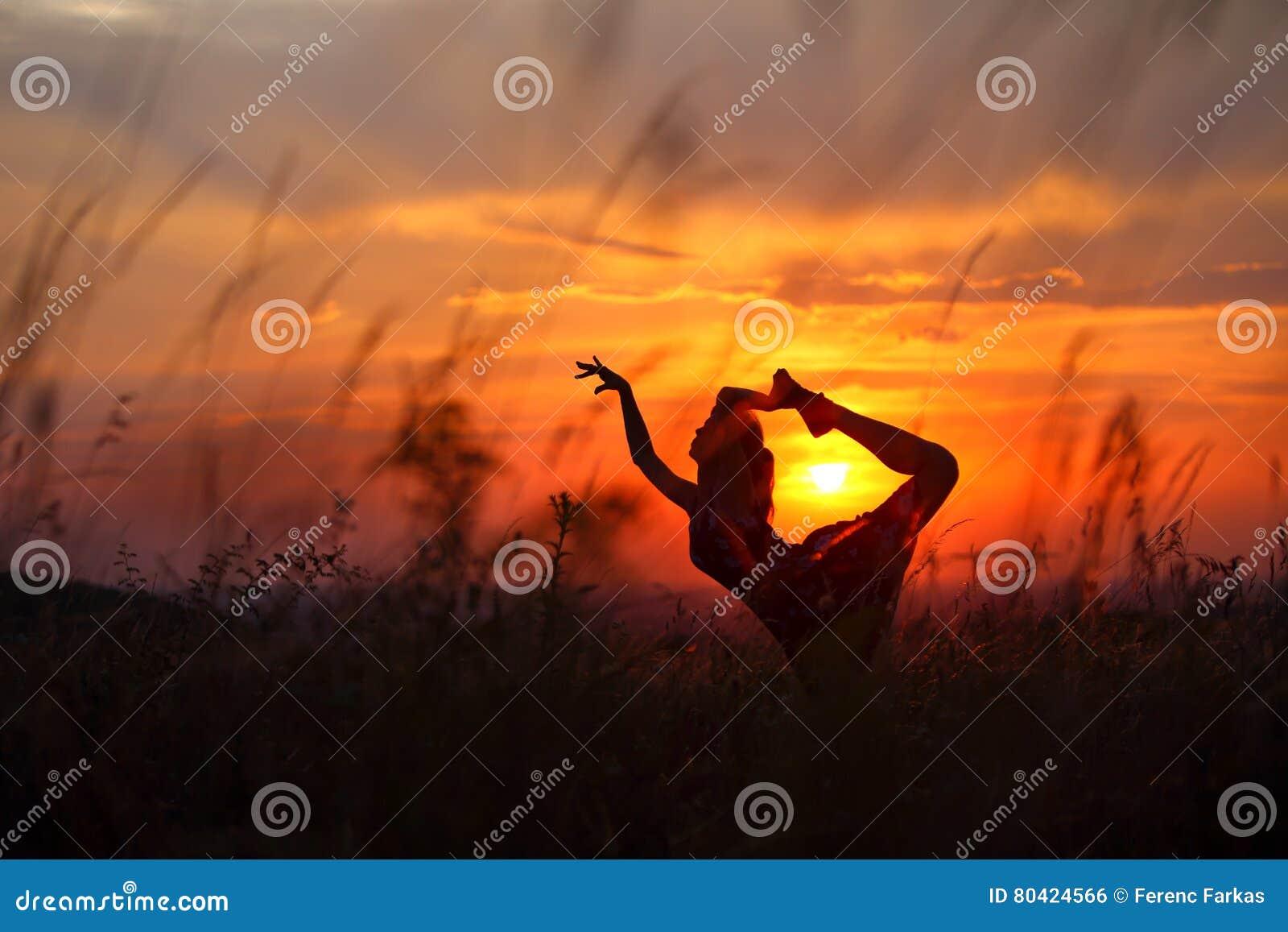 Jovem mulher que faz o movimento flexível da dança durante o por do sol