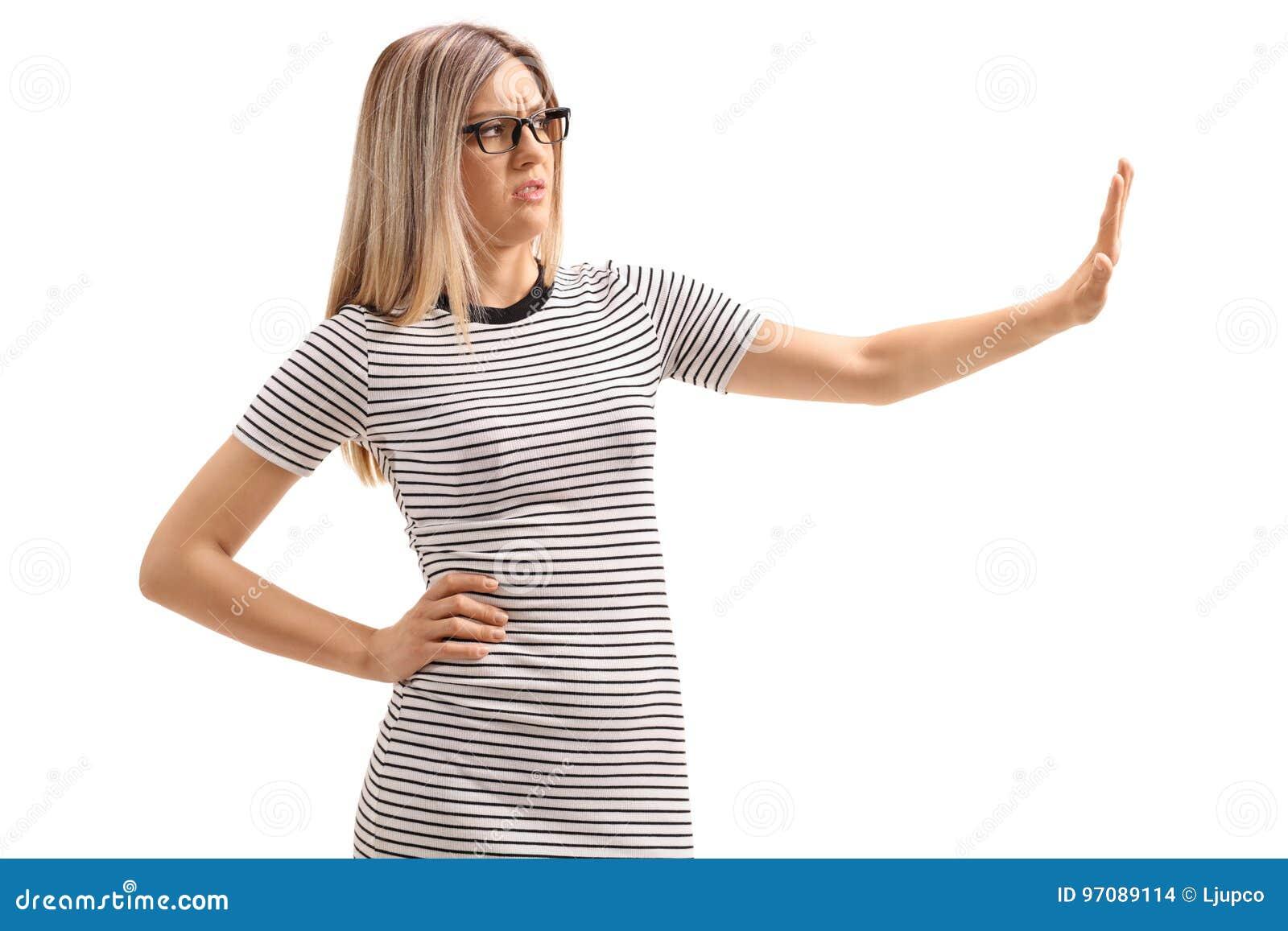 Jovem mulher que faz um gesto da recusa com sua mão