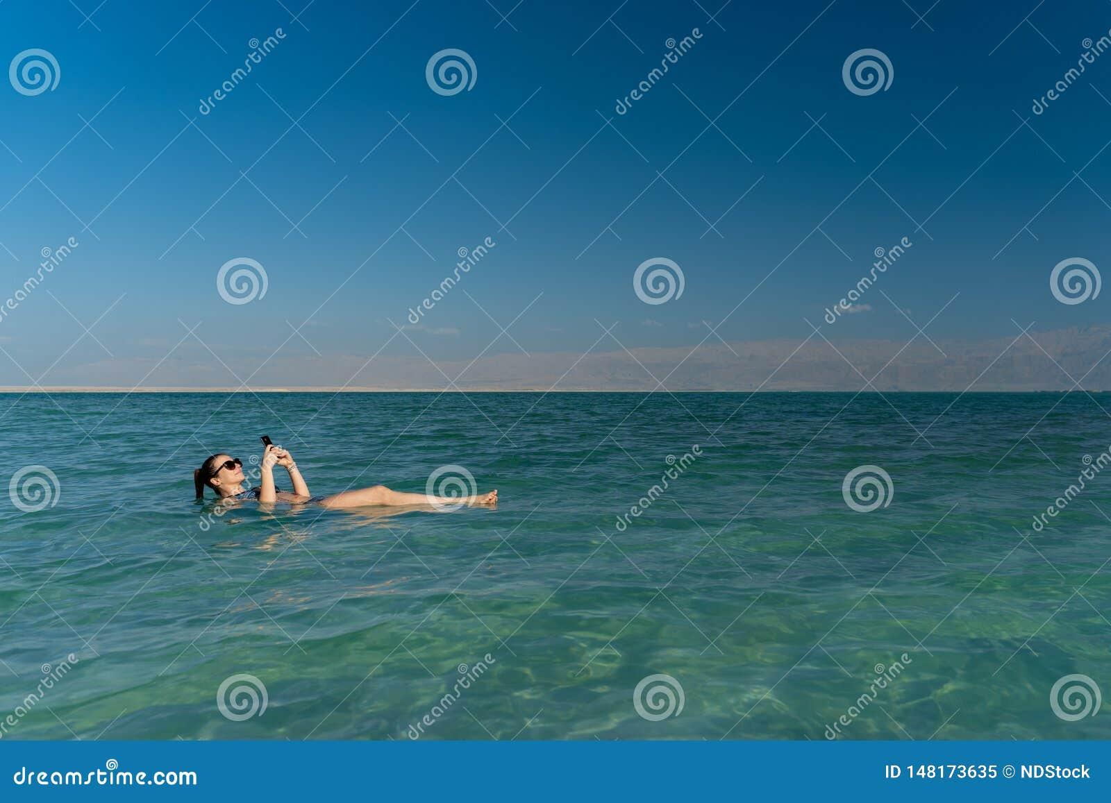 Jovem mulher que flutua na superf?cie da ?gua do Mar Morto e que usa seu smartphone