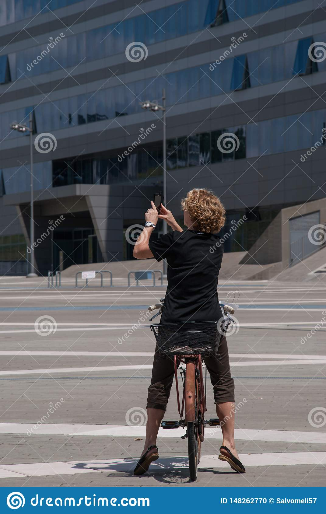 Jovem mulher que fotografa com um telefone celular