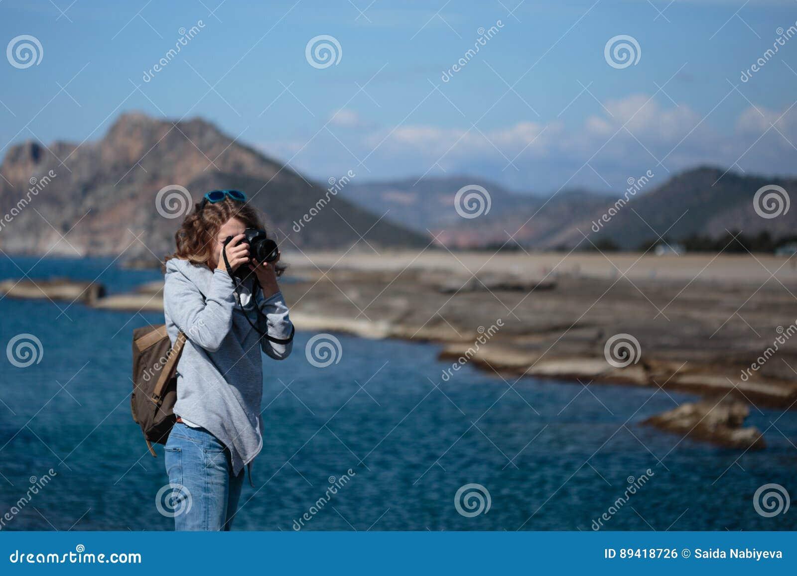 A jovem mulher que fotografa a rocha marcou a praia de Koru no Al de Gazipasha