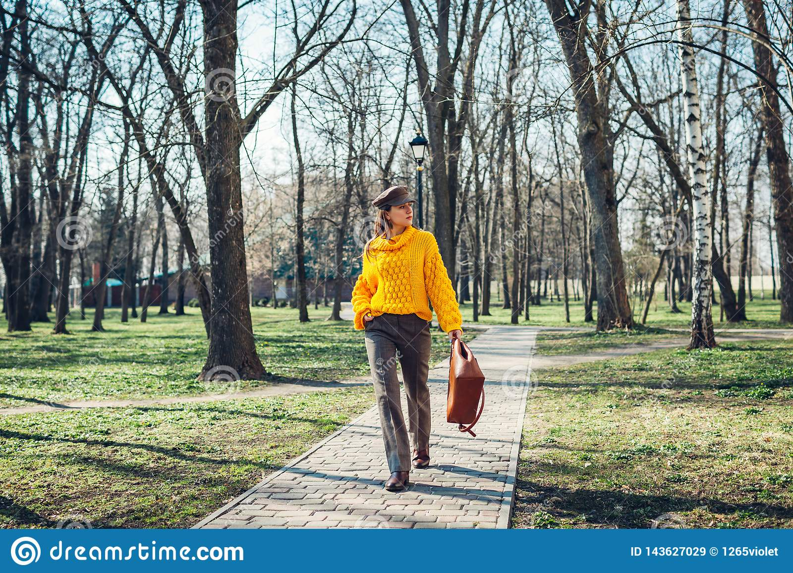 Jovem mulher que guarda a bolsa à moda e que veste a camiseta amarela Roupa e acessórios fêmeas da mola Forma