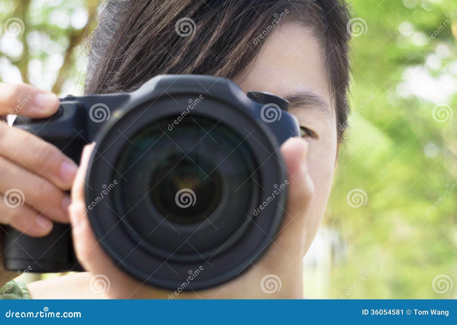 Jovem mulher que guarda a câmera da foto