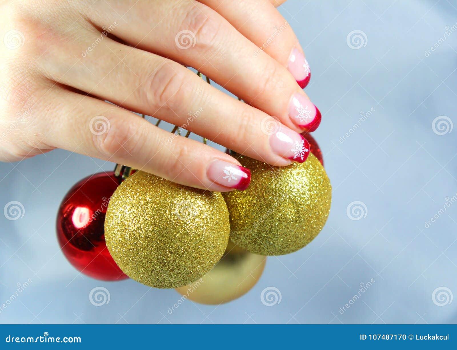 Jovem mulher que guarda ornamento do Natal em suas mãos