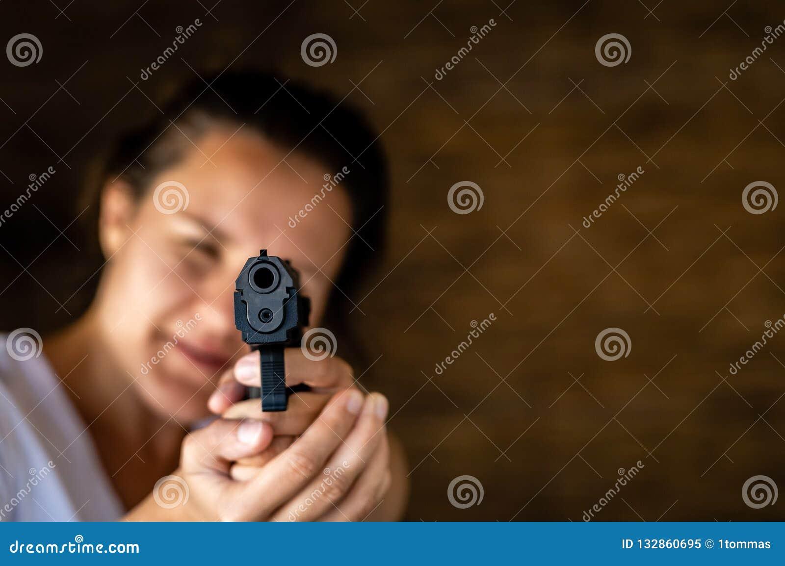 Jovem mulher que guarda uma arma e apontar