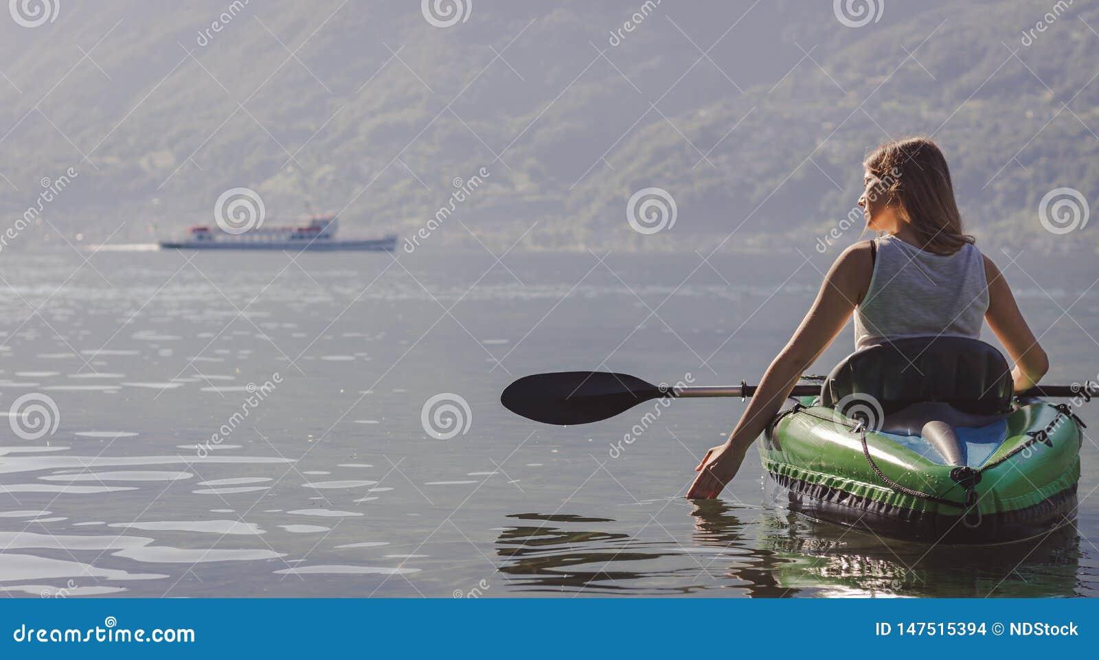 Jovem mulher que kayaking no lago