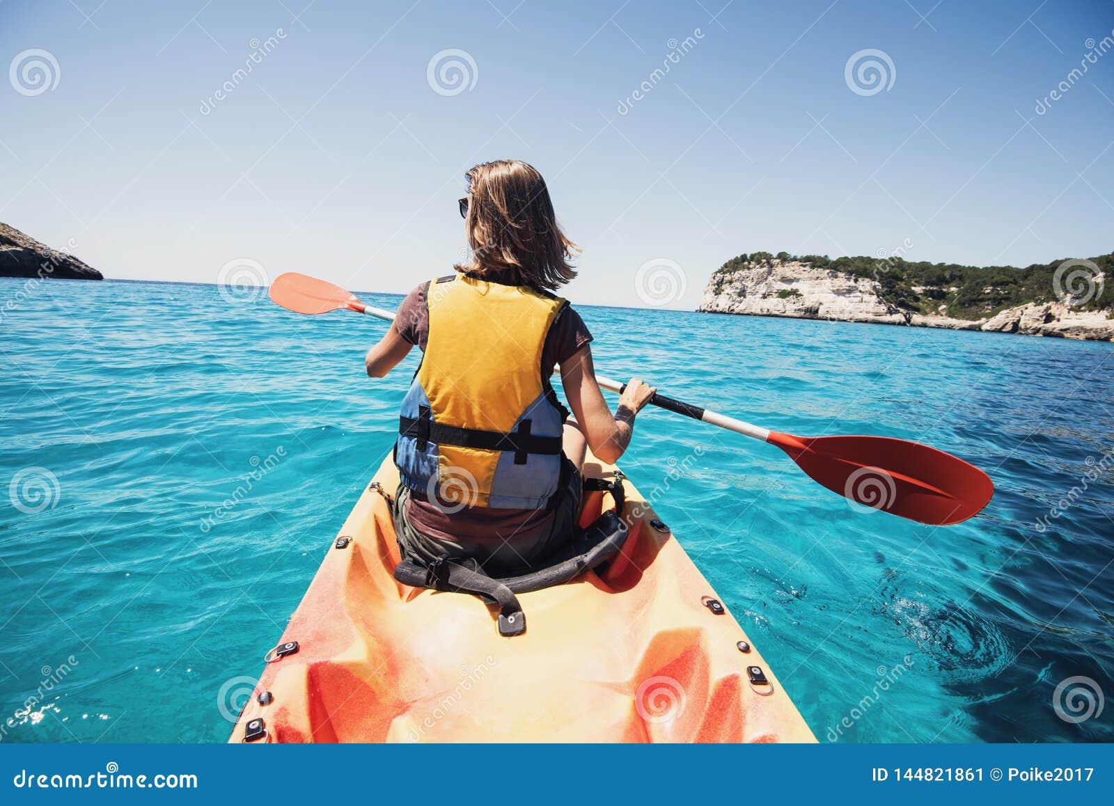 Jovem mulher que kayaking no mar Estilo de vida e conceito ativos do curso