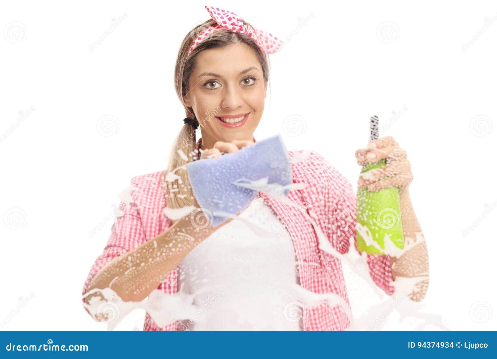 Jovem mulher que limpa uma janela com a toalha e o detergente