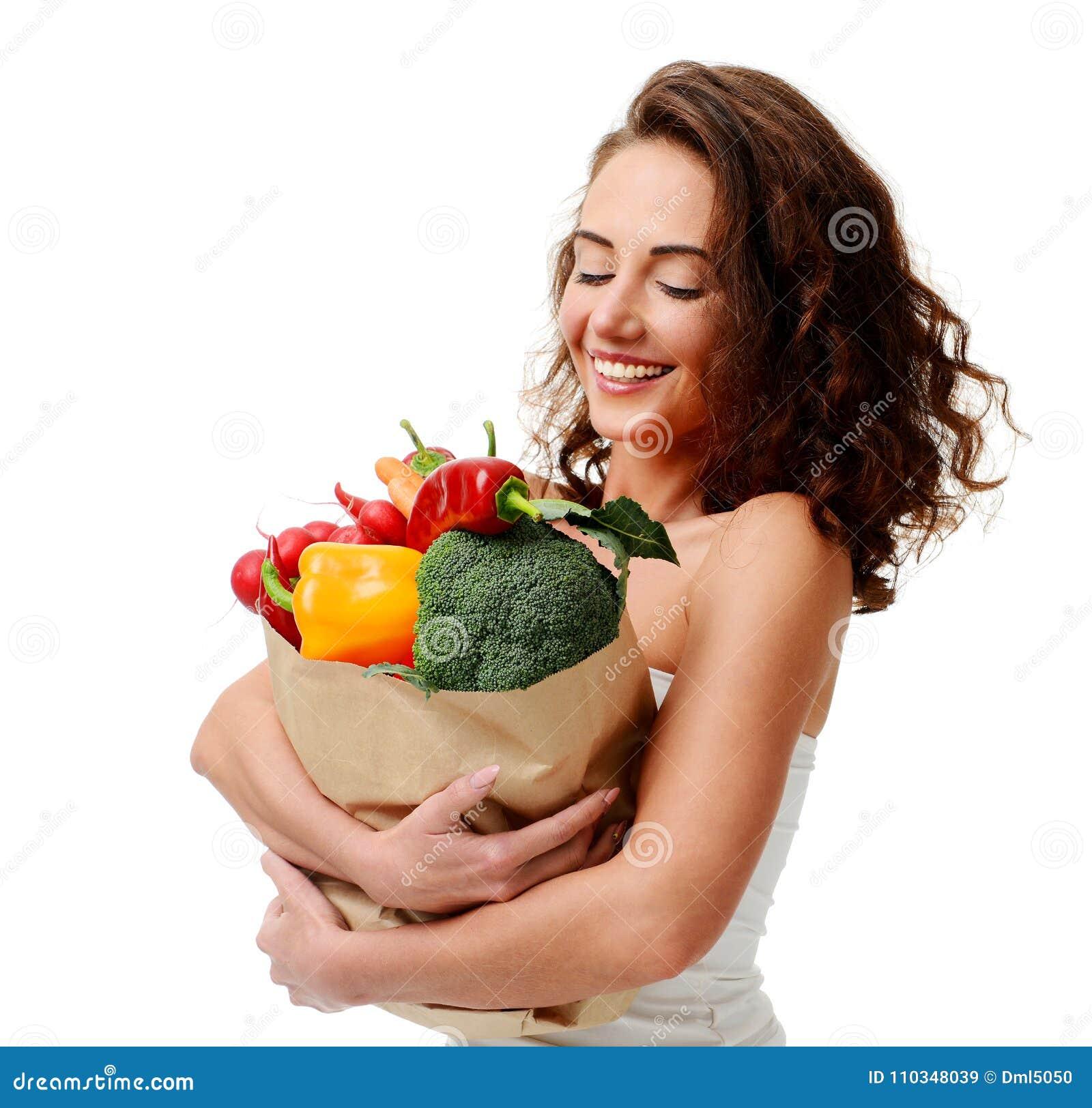 Jovem mulher que mantém o saco de compras de papel do mantimento completo de legumes frescos Conceito saudável comer da dieta