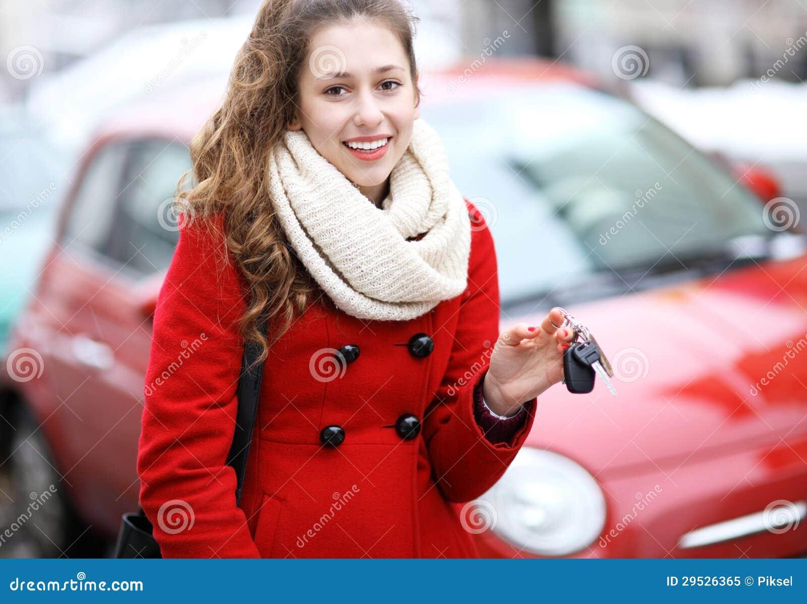 Jovem mulher que mostra a chave do carro