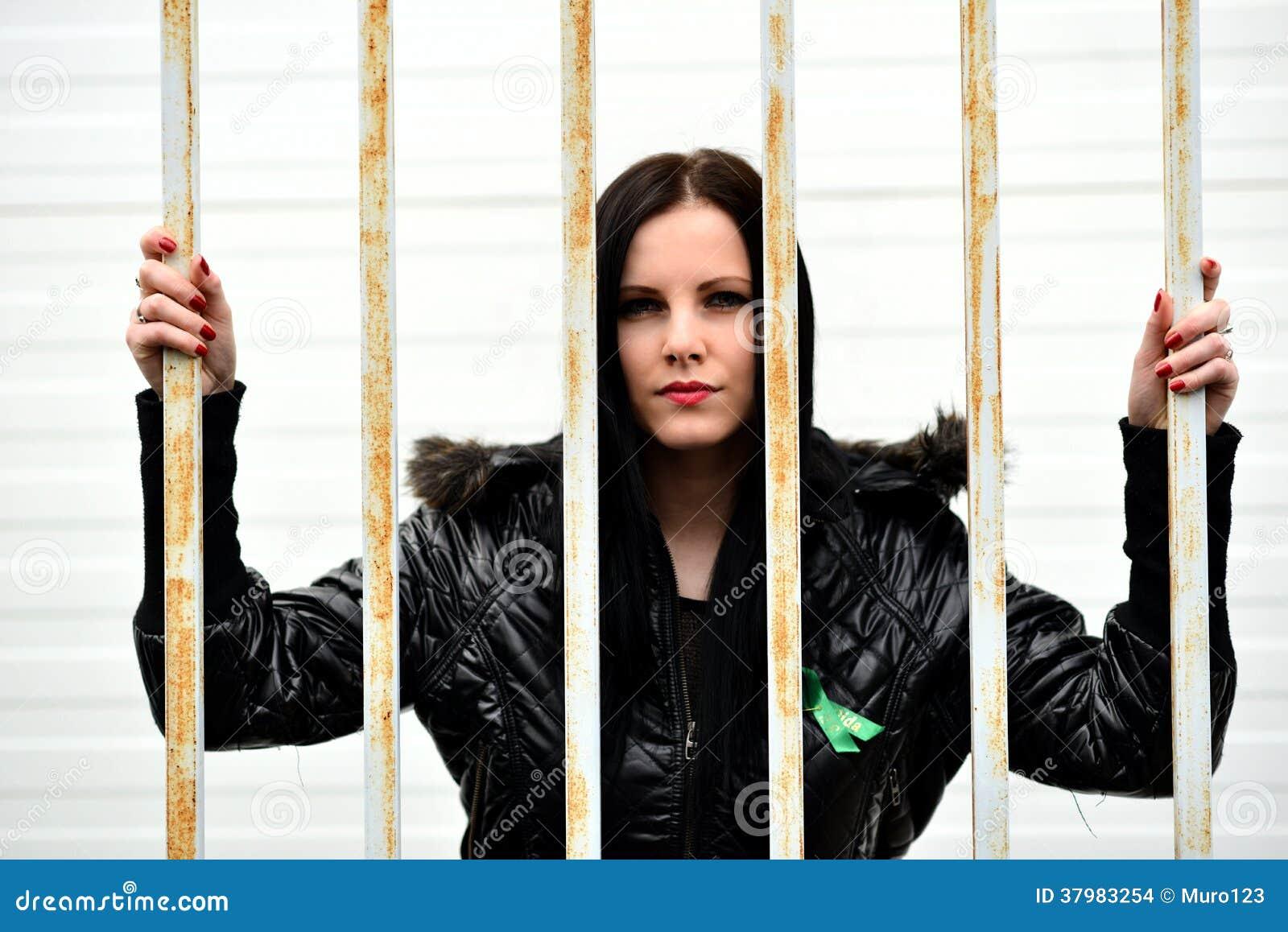 Jovem mulher que olha atrás das barras