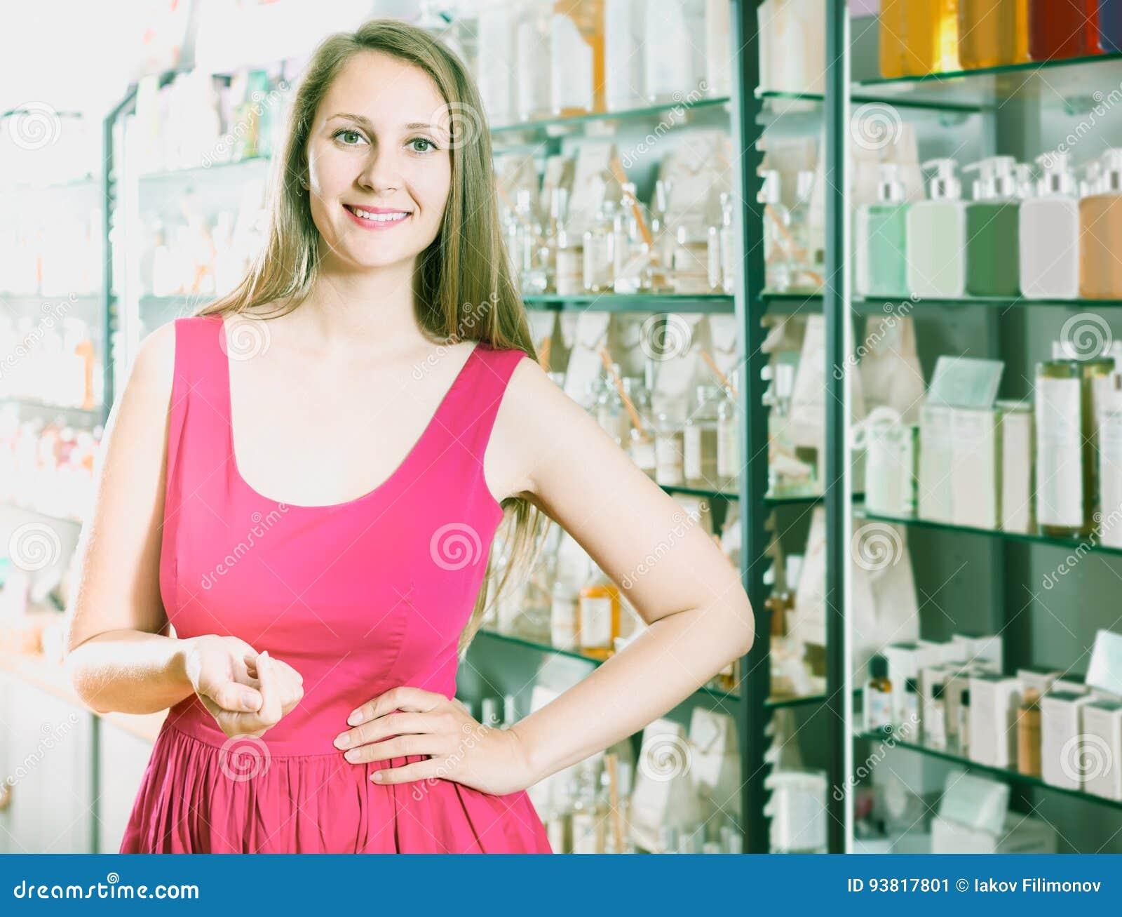 Jovem mulher que olha entusiasmado e que compra no supermarke do perfume
