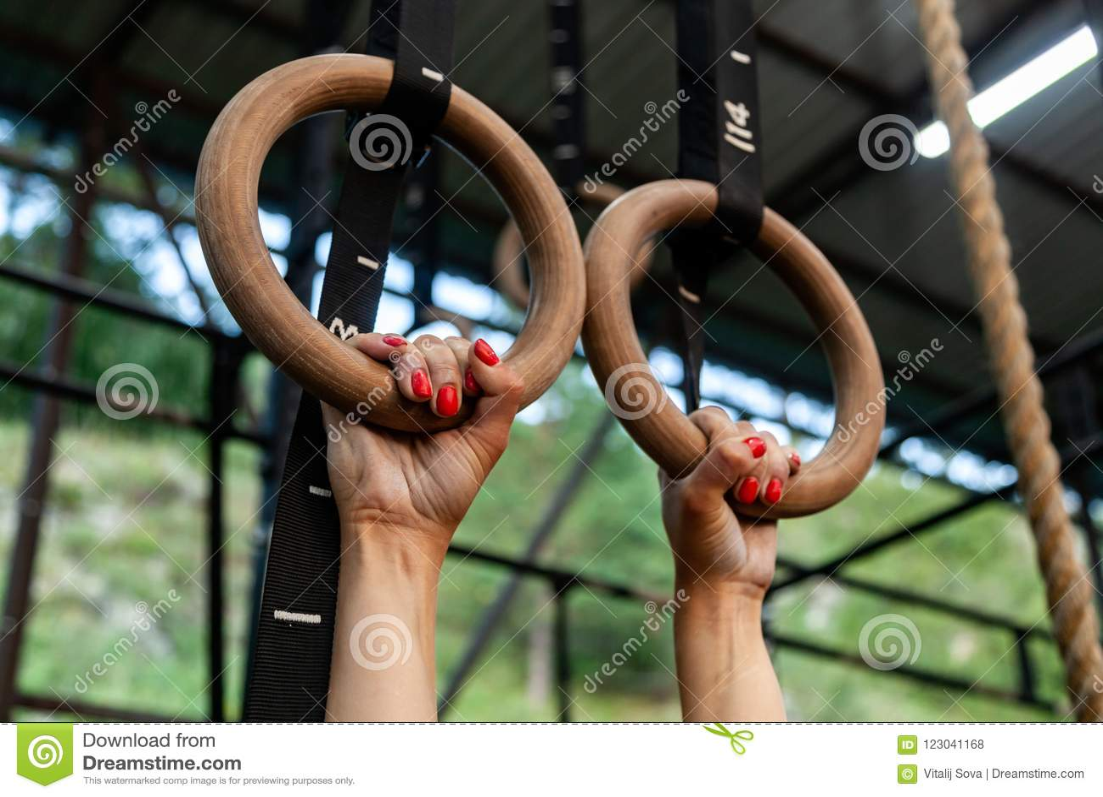 Jovem mulher que pendura em anéis do gym