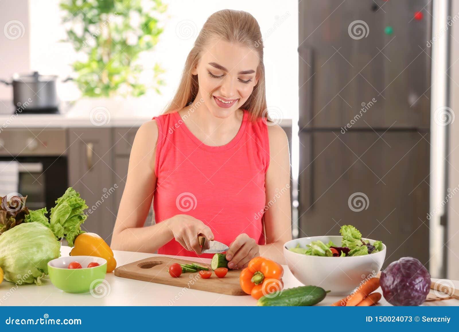 Jovem mulher que prepara a salada na cozinha Conceito do alimento da dieta