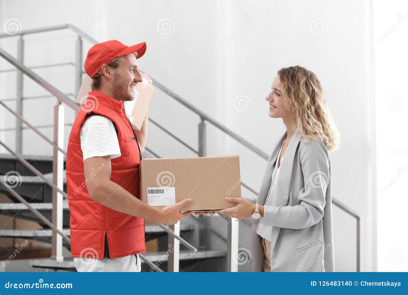 Jovem mulher que recebe o pacote do correio Foto de Stock
