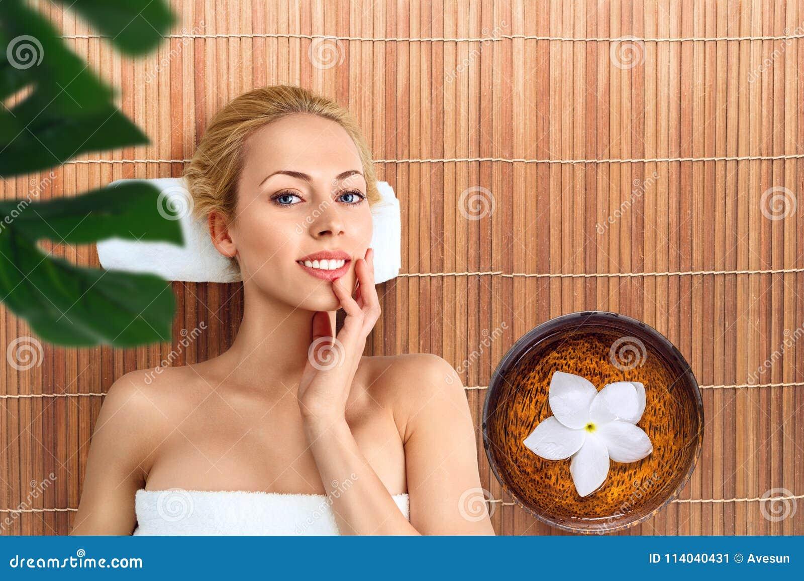 Jovem mulher que relaxa com massagem nos termas